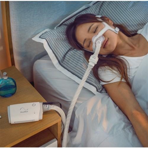 Woman sleeping with a AirMini AutoSet Travel CPAP Machine