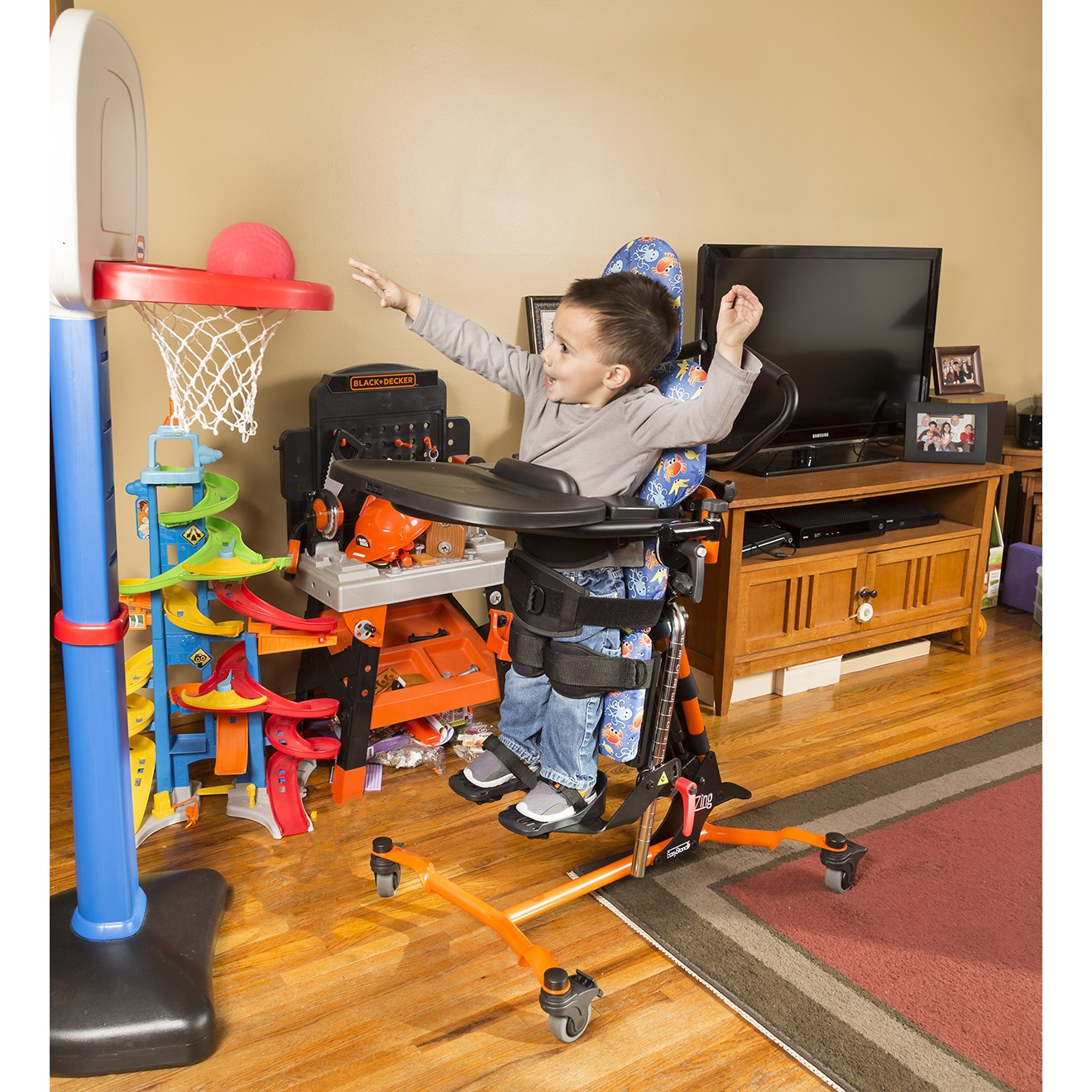 Child standing on a EasyStand Zing Supine TT Size 1 Playing Basketball