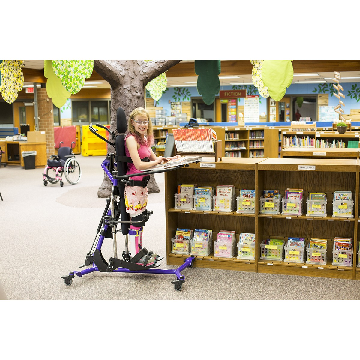 Girl standing in a Purple EasyStand Zing Supine TT Size 2 Gas Spring Lift in a Library