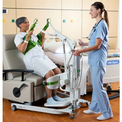 Woman sitting in slings of a Electric / Power Standing Patient Lift