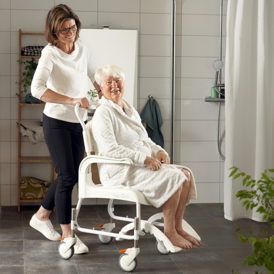 Woman sitting in a Etac Clean Height Adjustable Shower Commode