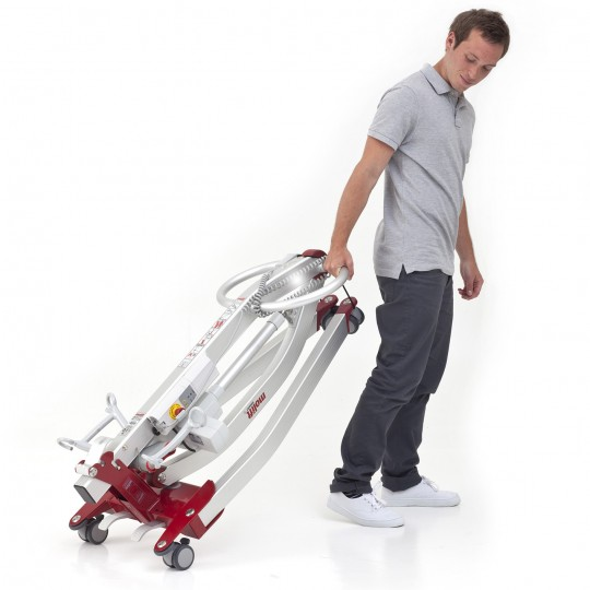 Man pulling a folded Etac Molift Smart 150 Portable Electric Patient Lift