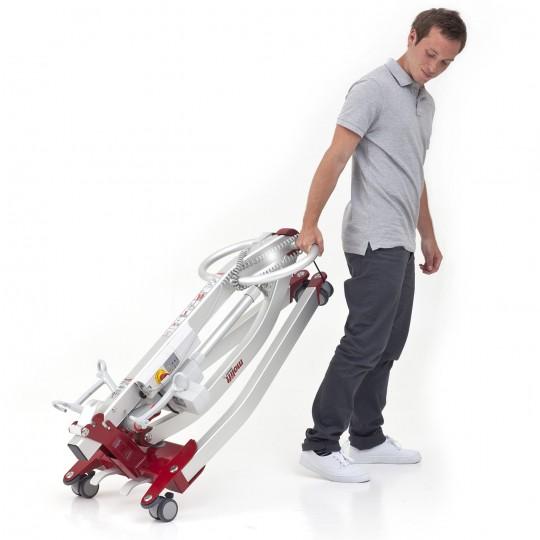 Man pulling a folded Etac Molift Smart 150 Portable Electric Patient Lift