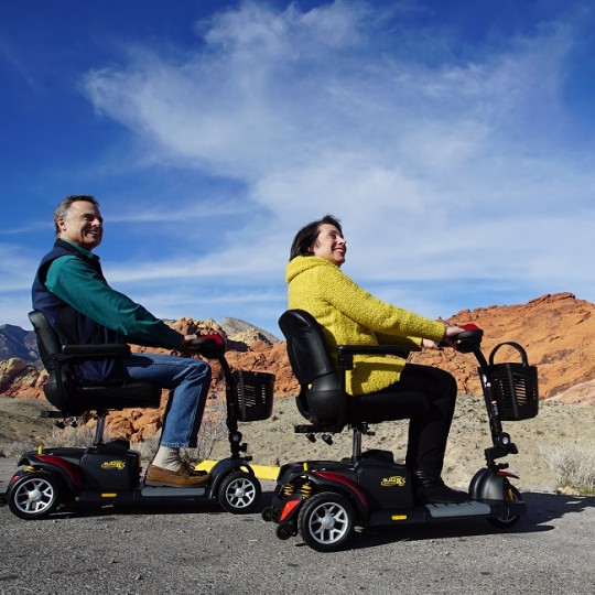 Two people sitting in Golden Tech Buzzaround EX 3-Wheel Mobility Scooters