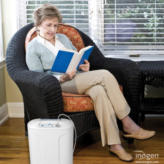 Woman sitting on Chair reading a book with Inogen At Home Oxygen Concentrator