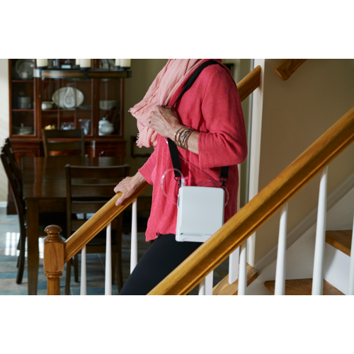 Woman walking down stairs with Inogen One G5 Portable Oxygen Concentrator