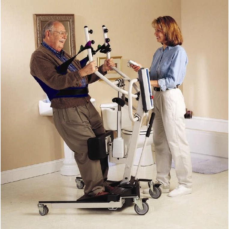 Man sitting in sling of an Invacare Reliant 350 Electric Sit-To-Stand Lift