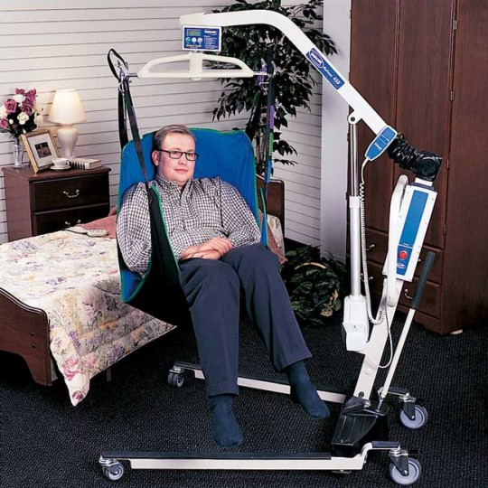 Man sitting in sling of a Invacare Reliant Plus 450 Low Base Electric Patient Lift