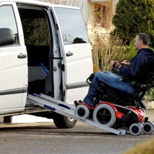 Man sitting in LEVO C3 Standing Power Wheelchair going Up a Ramp