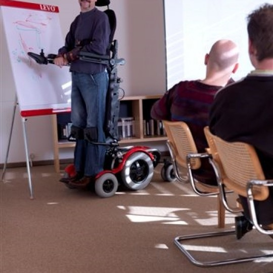 Man standing in a LEVO C3 Standing Power Wheelchair giving a presentation