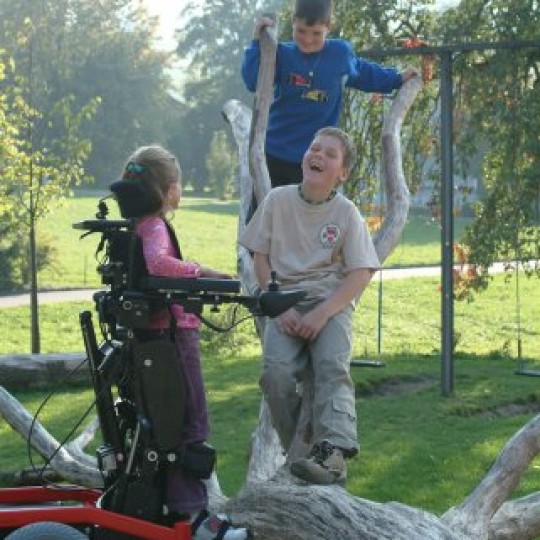 Child sitting in LEVO Combi Jr Standing Power Chair at park
