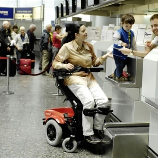 Woman sitting in a Levo Combi Standing Power Wheelchair at the airport