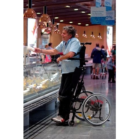 Man sitting in a LEVO LCEV Standing Manual Wheelchair while shopping
