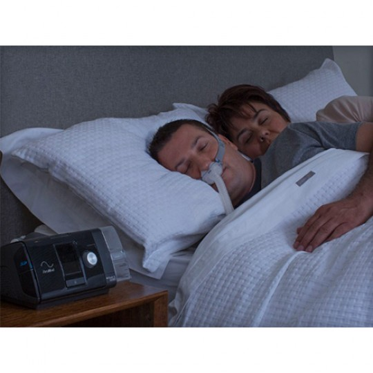 Man laying in bed using a ResMed AirSense 10 AutoSet CPAP with HumidAir