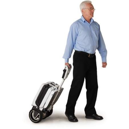 Man lugging a Moving Lift Atto Folding Mobility Scooter as Suitcase
