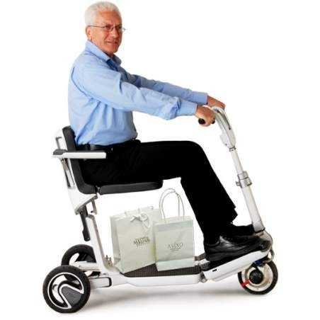 Man sitting in White Moving Lift Atto Folding Mobility Scooter