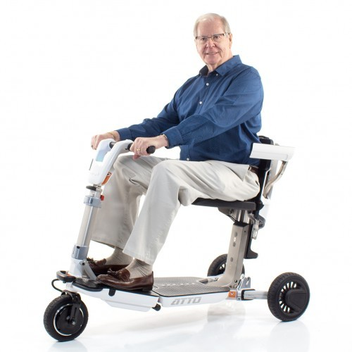 Man sitting in a Moving Lift Atto Folding Mobility Scooter