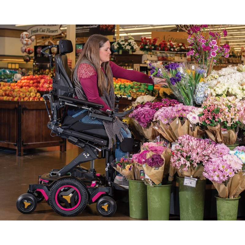 Woman sitting in Permobil M3 Corpus Mid Wheel Power Wheelchair Picking Flowers