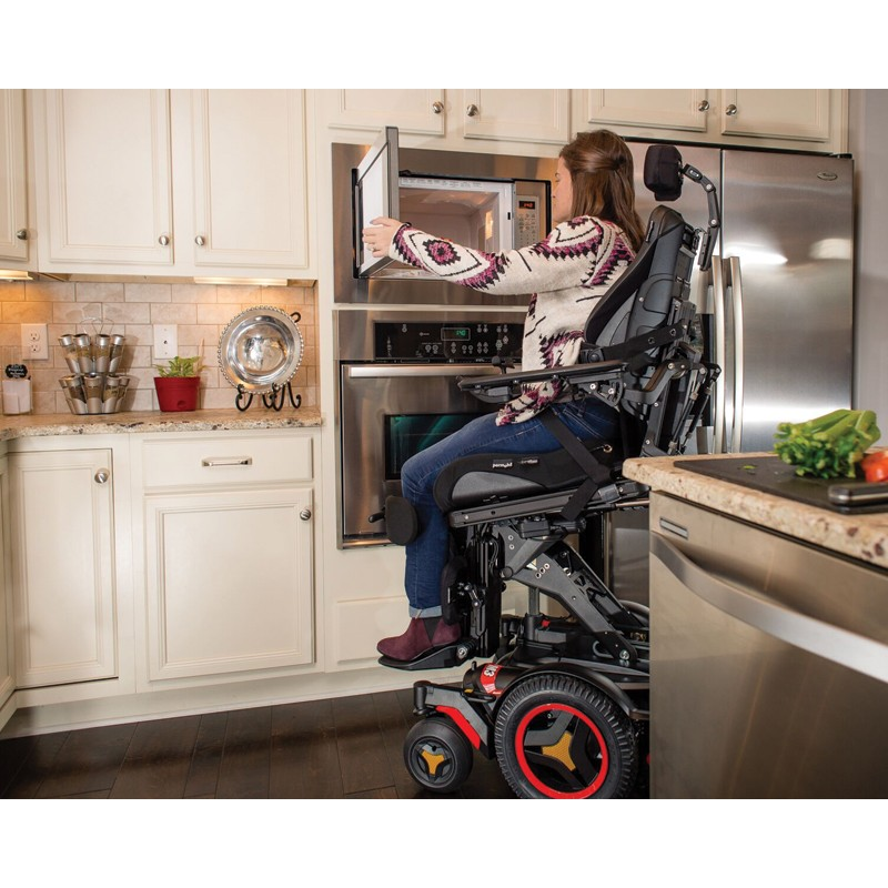 Woman sitting in Permobil M3 Corpus Mid Wheel Power Wheelchair Cooking in Kitchen
