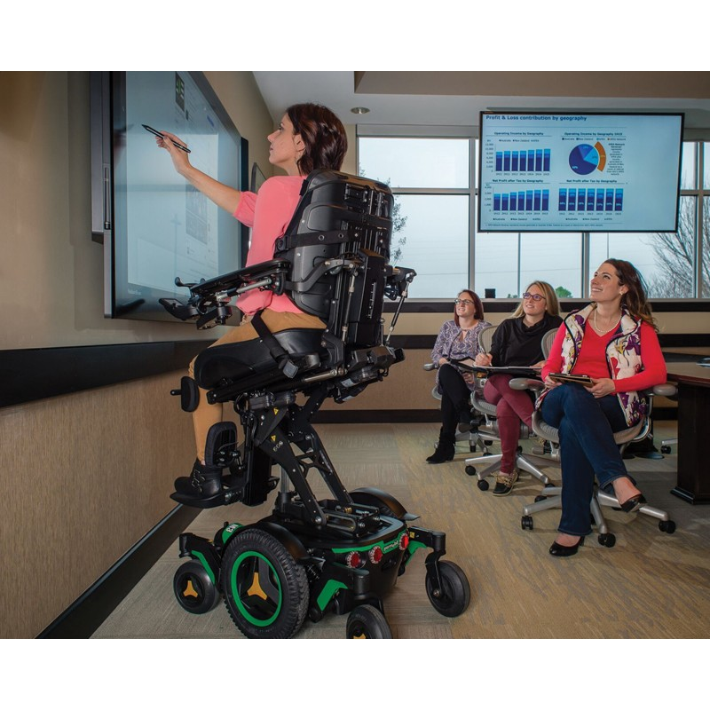 Woman sitting in Permobil M3 Corpus Mid Wheel Power Wheelchair giving a Presentation