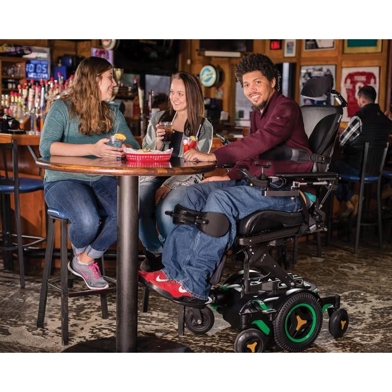 Man sitting in Permobil M3 Corpus Mid Wheel Power Wheelchair at a bar