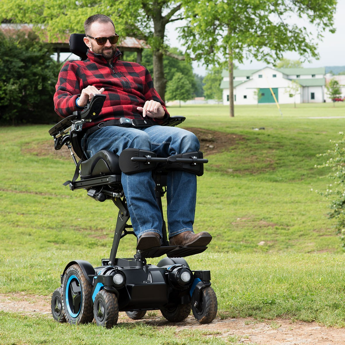Man sitting in Permobil M5 Corpus Mid Wheel Power Wheelchair Outside