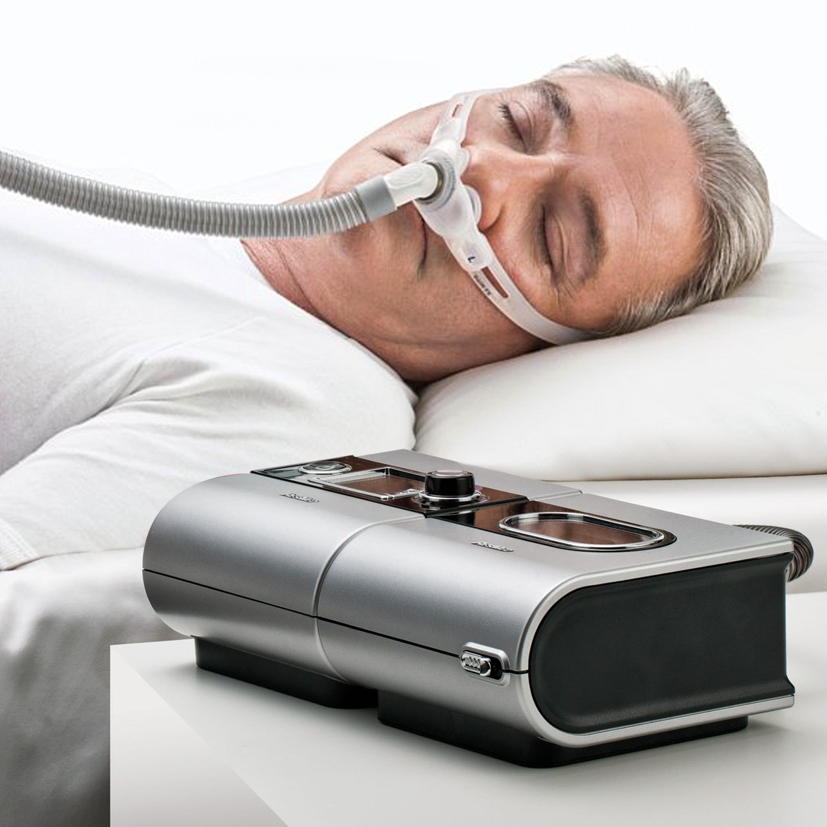 Man sleeping with a Swift FX Nasal Pillow CPAP Mask with Headgear