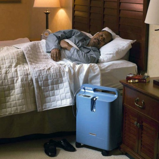Man sleeping with Respironics Everflo Q Stationary Oxygen Concentrator Next to Bed