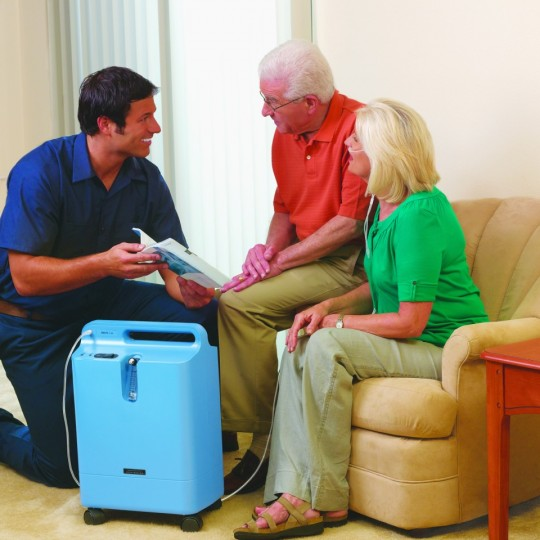 Woman and Man sitting on couch with Respironics Everflo Q Stationary Oxygen Concentrator