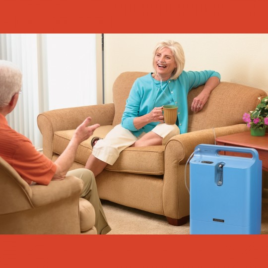 Woman sitting on Cough with Respironics Everflo Q Stationary Oxygen Concentrator Next to her