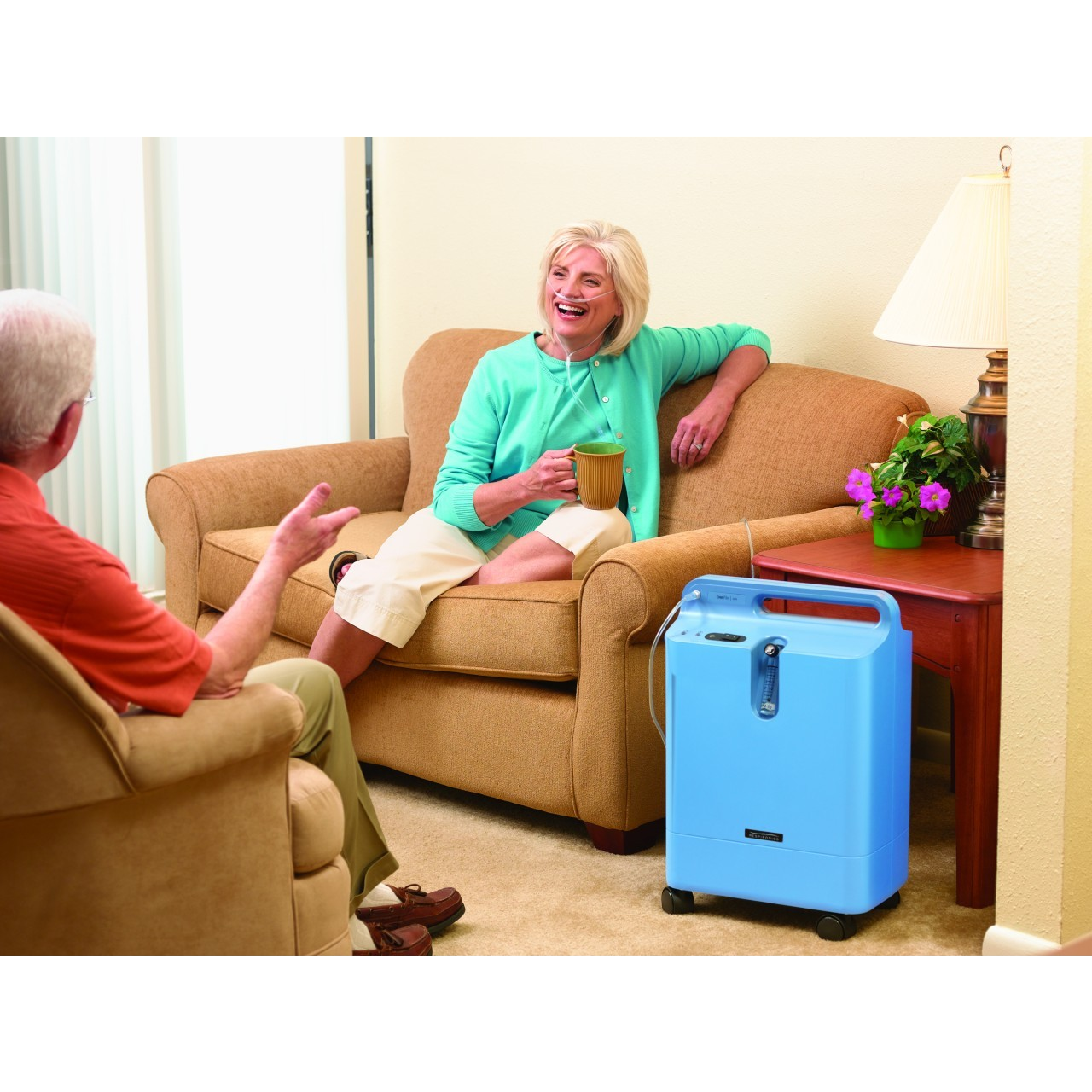 Woman sitting on couch with Respironics Everflo Stationary Oxygen Concentrator