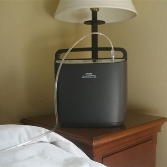 Black Respironics SimplyFlo Stationary Oxygen Concentrator Next to Bed