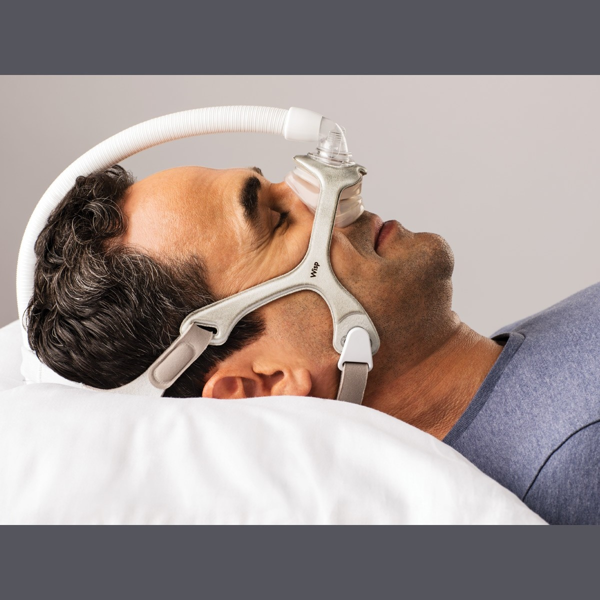 Man sleeping with a Wisp Nasal CPAP Mask with Headgear