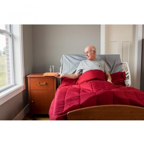 Man laying in Comfort Wide EX5000 Expandable Width Long Term Care Low Bed