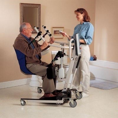 Man sitting in sling of Hydraulic Stand Up Patient Lift Rental