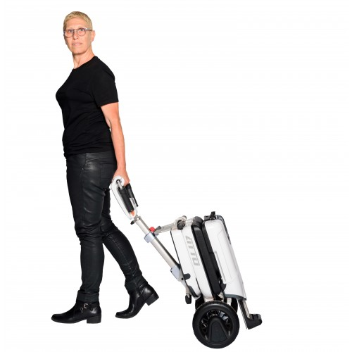 Woman lugging a Moving Life ATTO Folding Mobility Scooter