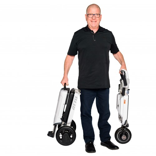 Man holding a Folded Moving Life ATTO Folding Mobility Scooter
