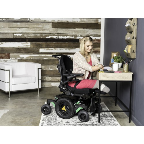 Woman sitting in Permobil M1 Mid Wheel Power Wheelchair at a desk