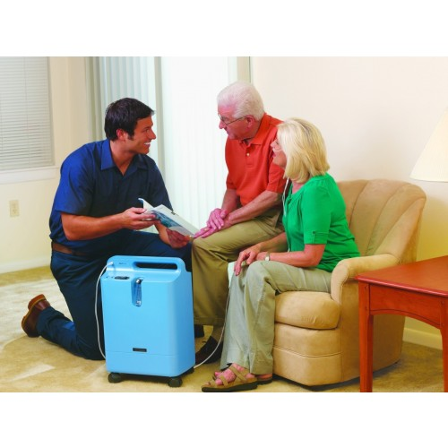 Woman sitting on couch using a Respironics Everflo Q Stationary Oxygen Concentrator