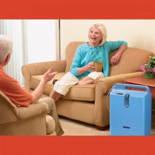 Woman sitting on a couch while using a Respironics Everflo Q Stationary Oxygen Concentrator